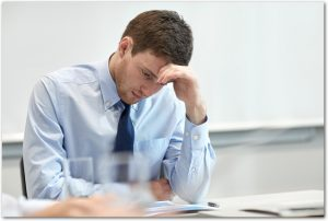 business, people and crisis concept - businessman sitting sad and solving problem in office